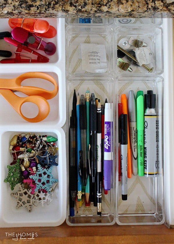 Clear plastic dividers help organize a junk drawer