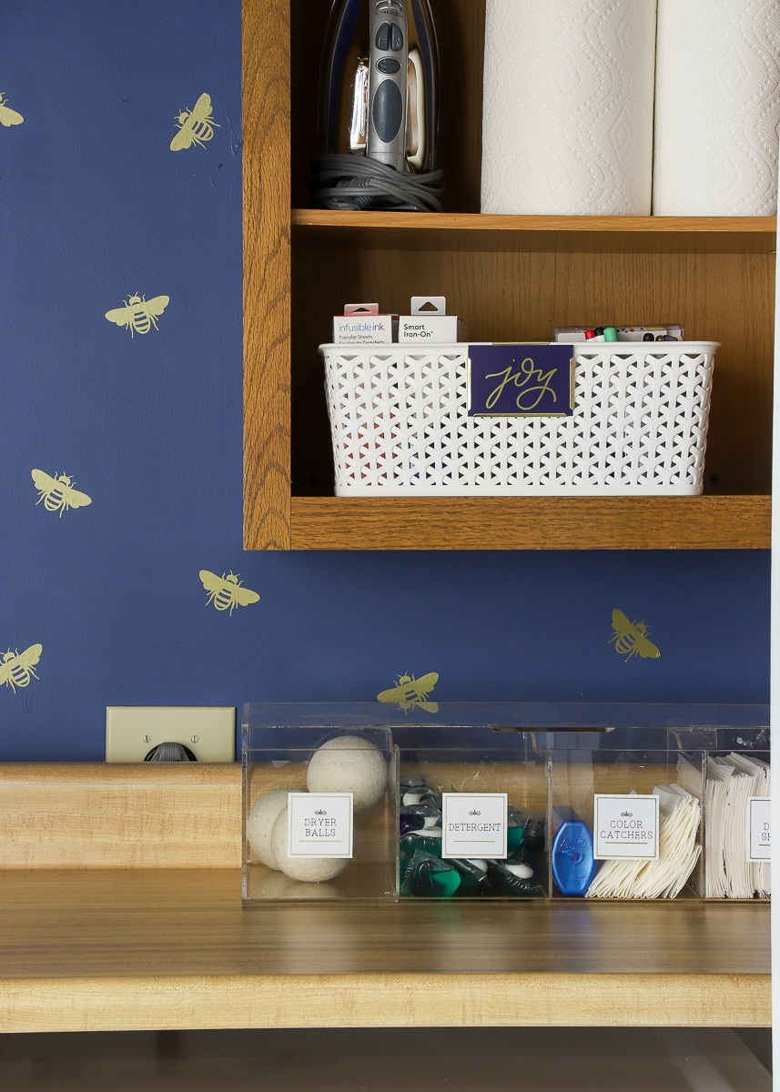 laundry room with various clear plastic storage containers with labels