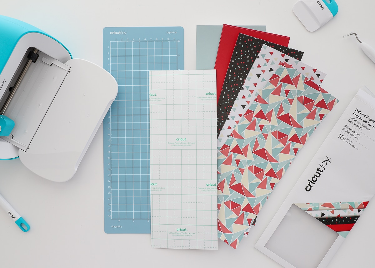 cricut joy machine with various cricut papers and supplies
