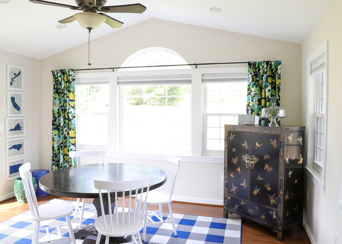 dining room with green and yellow patterned curtains. hanging below an arched window