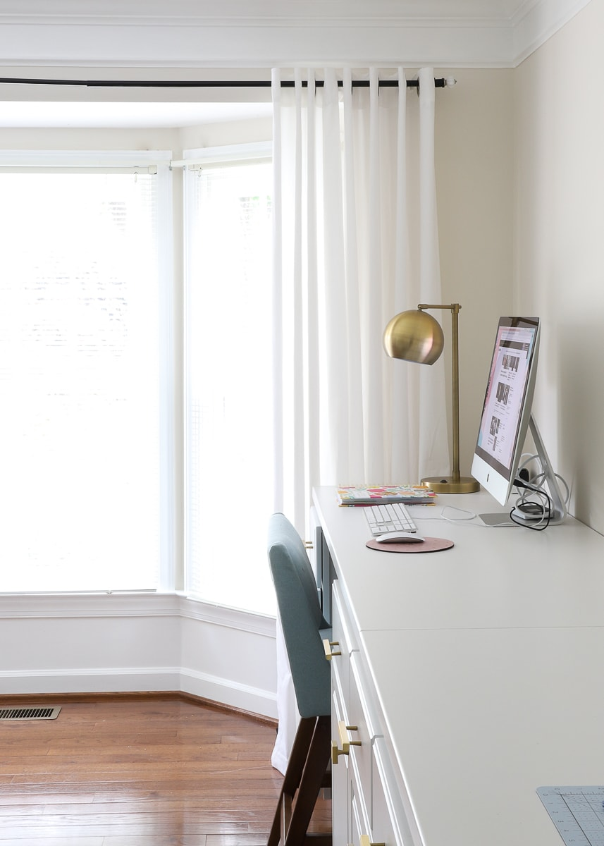 white curtains hanging in a bay window in a home office