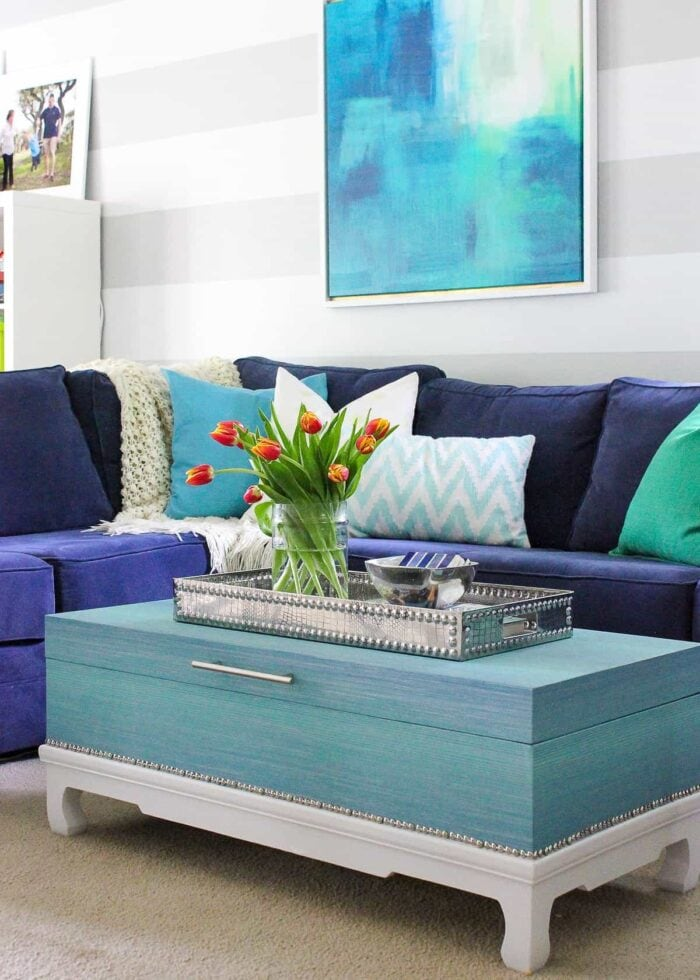 Navy sectional with turquoise grasscloth coffee table