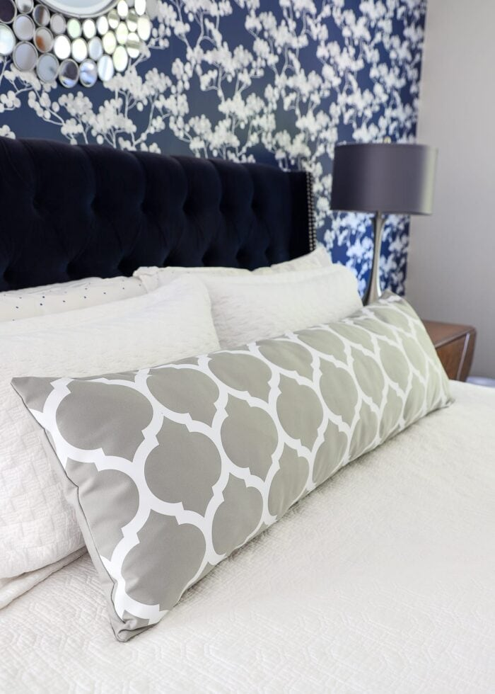 Grey custom bolster pillow made with Cricut Smart Iron-on on a white bed against a blue wall