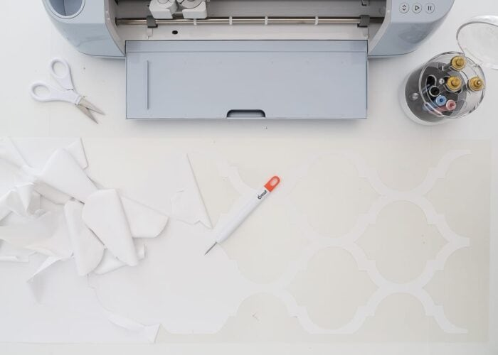 Use a weeding tool to pull away the excess from the Cricut Smart Iron-On design