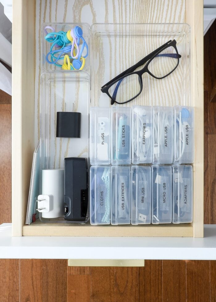 Desk drawer with organized cords and plugs