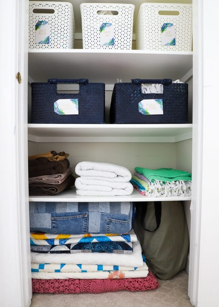 Folded and stacked towels and blankets on a linen closet shelf.