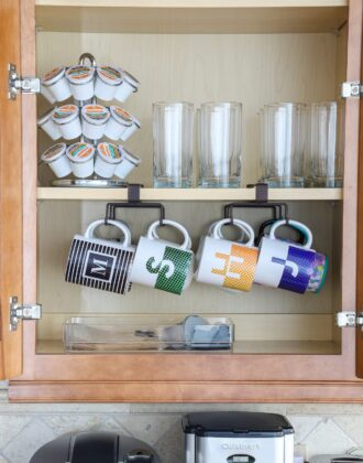 Kitchen cabinet with organized coffee mugs and supplies