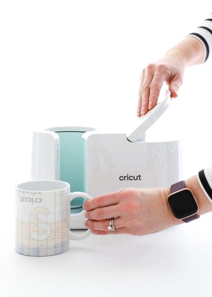 Split monogram mug next to Cricut Mug Press