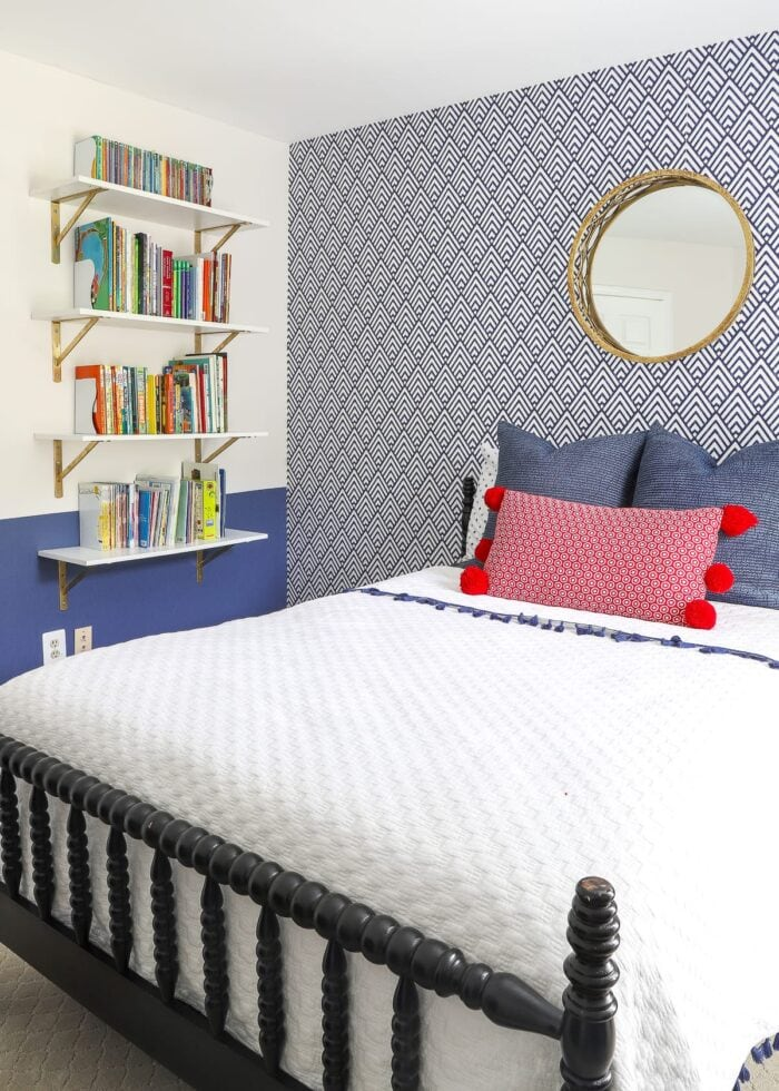 Bedroom with navy wallpaper, white bedding and floating bookcase