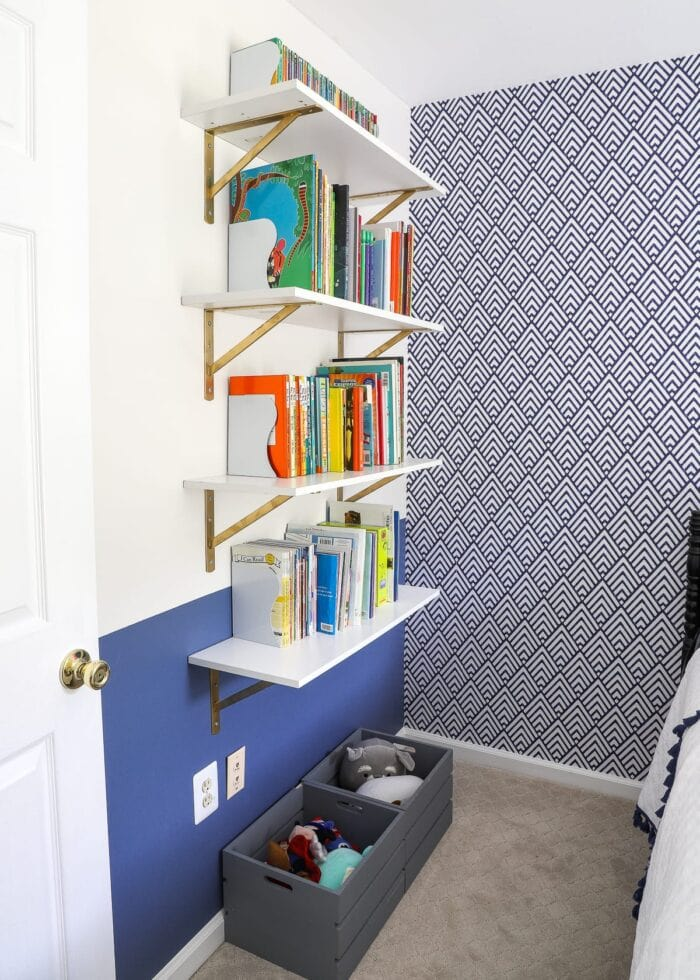 White shelf with gold brackets, white bookends and kids books.