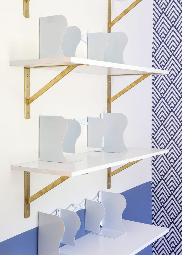 White shelf with gold brackets, and white bookends.