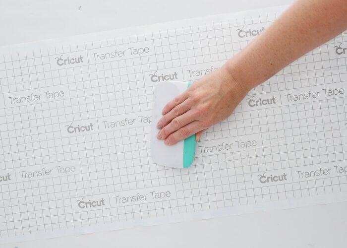 Hand using tool over Cricut Transfer Tape