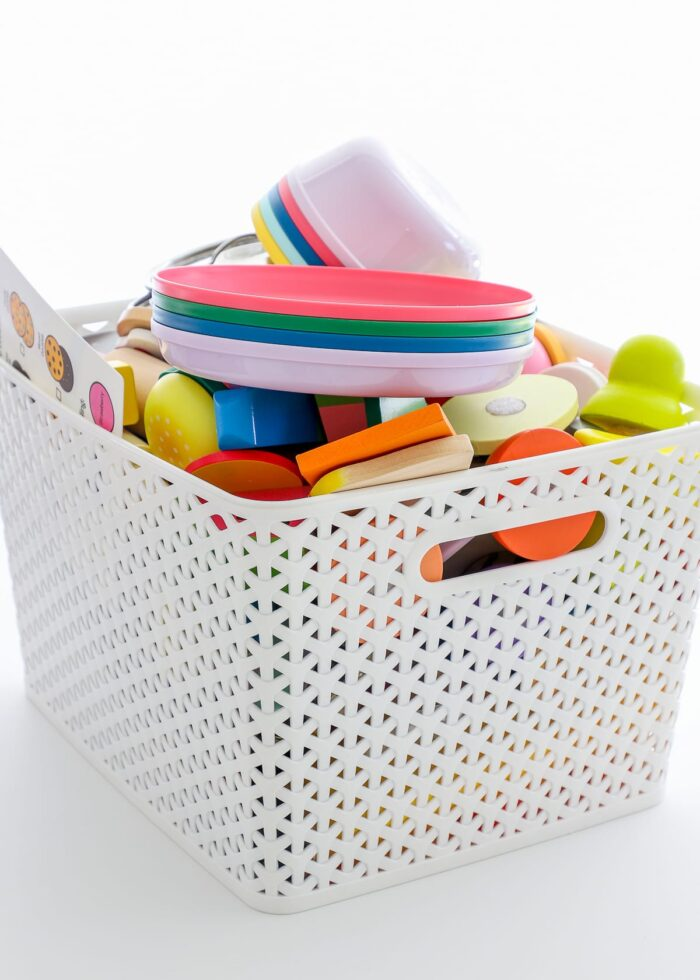 A messy basket full of play food and kitchen items.