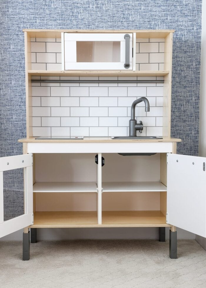 An IKEA play kitchen with empty cabinets