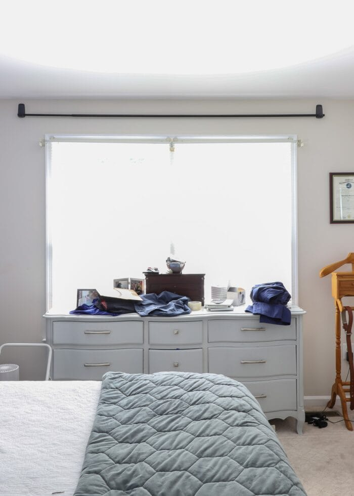 Command Hooks holding up a curtain rod above a window.
