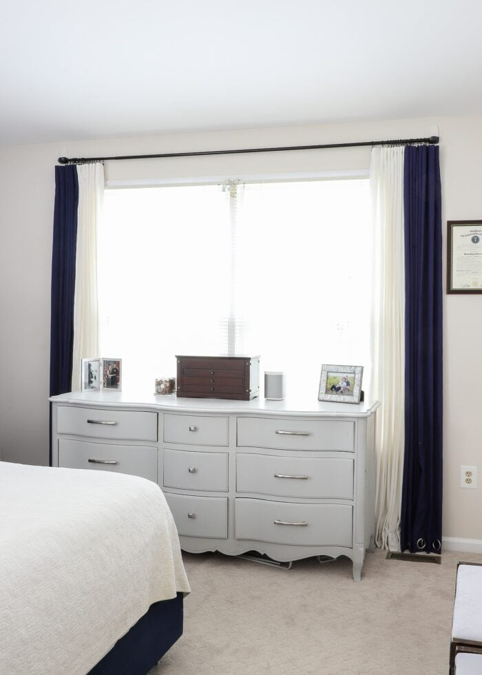 Window with navy and white curtains hung on Command Hooks around a grey dresser.
