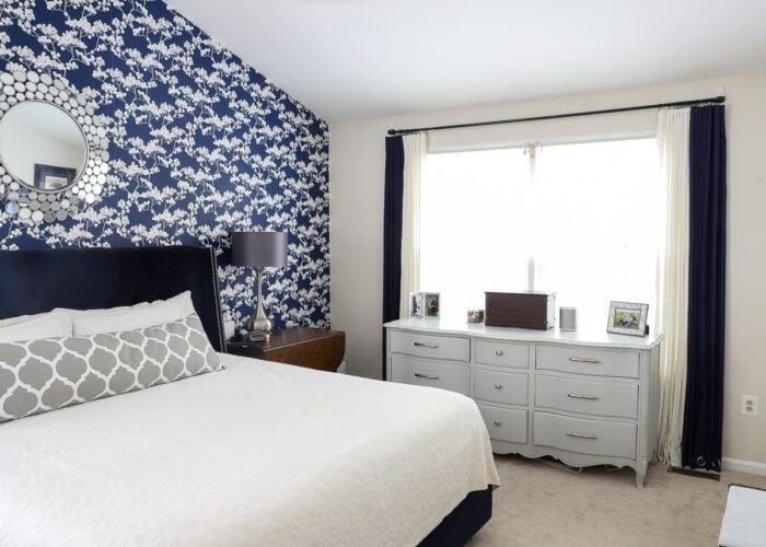 Bedroom with blue wallpaper and a curtain rod hung with Command Hooks