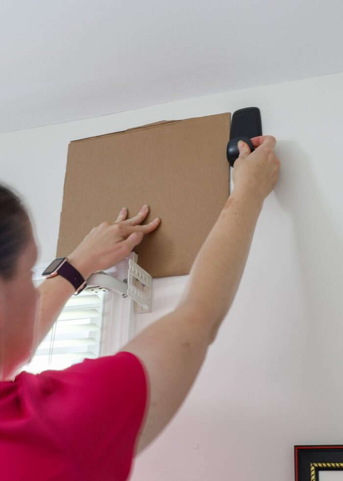 Using a cardboard template to hang a Command Hook above a wall.