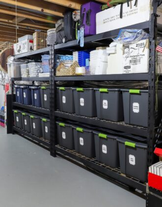 Vertical picture of black metal storage shelves in a rental home loaded with bins, baskets, and boxes.
