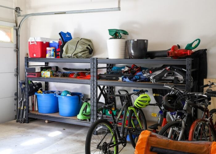 Garage with black metal shelving loaded with toys and bikes.