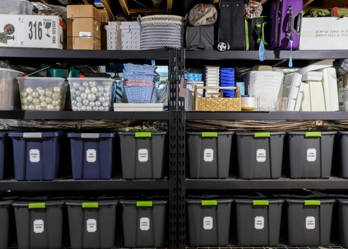 Horizontal picture of black metal storage shelves loaded with bins, baskets, and boxes.