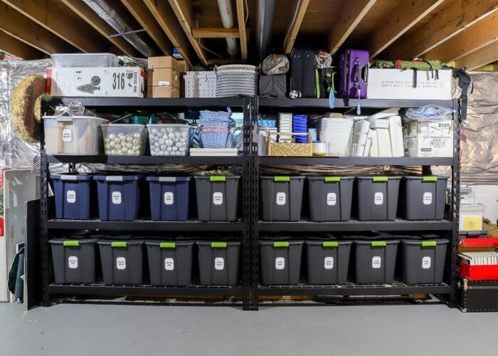Horizontal picture of black metal storage shelves in a rental loaded with bins, baskets, and boxes.