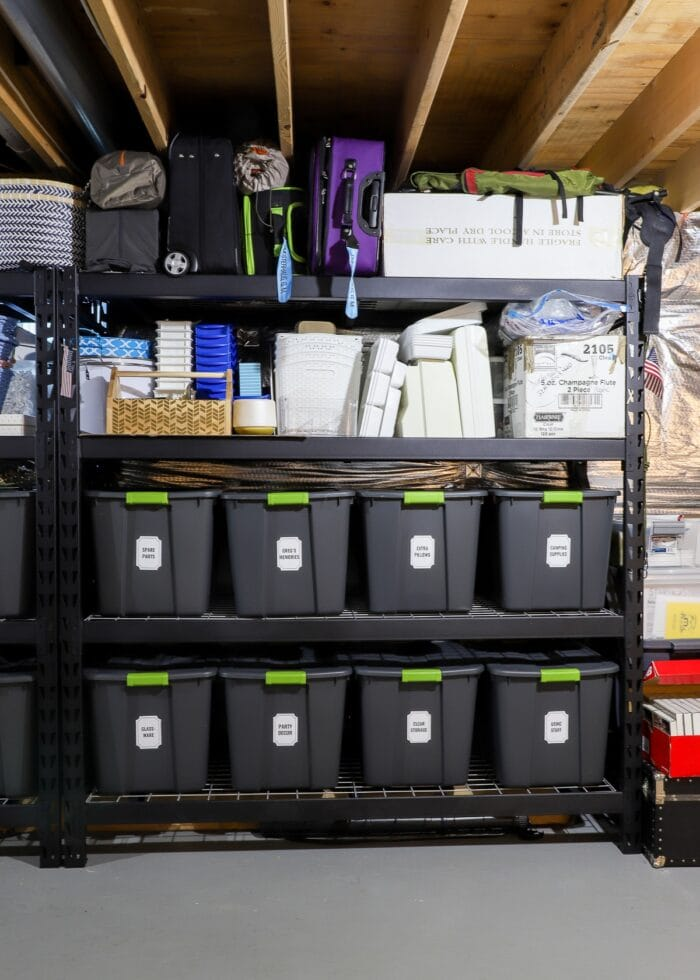 Vertical picture of black metal storage shelves in a rental loaded with bins, baskets, and boxes.
