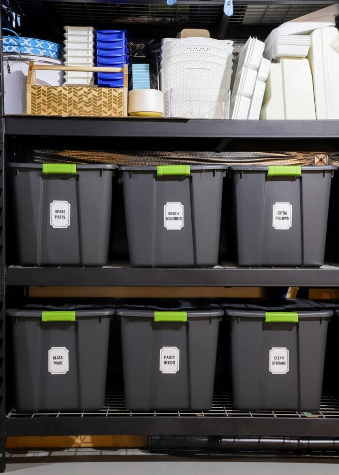 Vertical picture of black metal storage shelves loaded with grey bins and white labels.