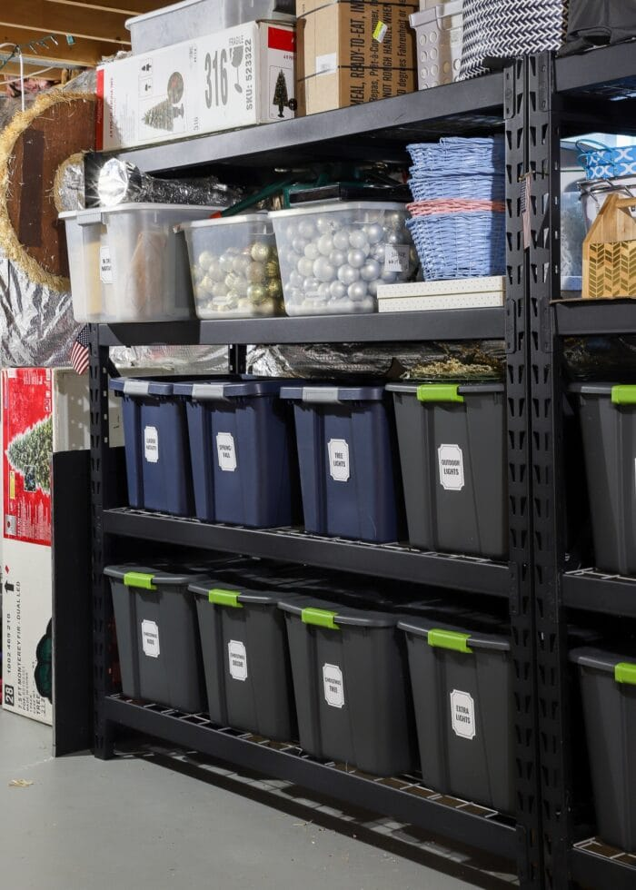 Vertical picture of black metal deep storage shelves in a rental loaded with bins, baskets, and boxes.