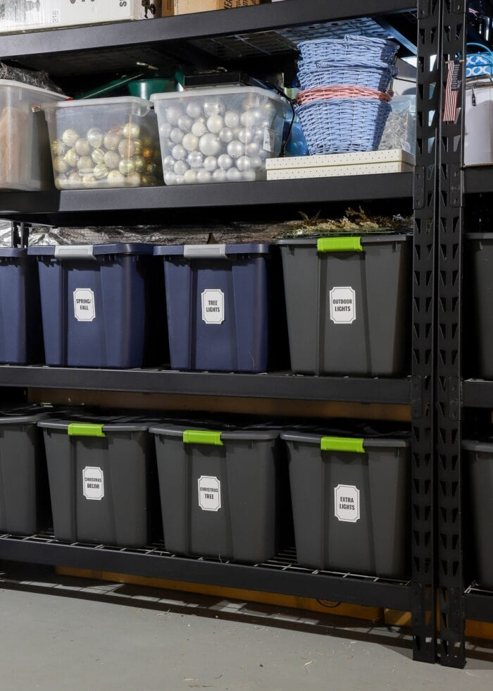 Vertical picture of black metal deep storage shelves in a rental home loaded with bins, baskets, and boxes.