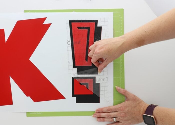 Hands using transfer tape to layer red and black vinyl letters