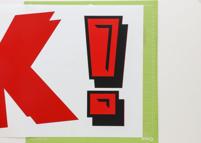 Exclamation point cut from red and black vinyl and layered together