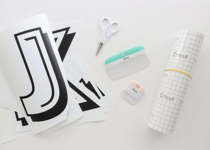 Supplies needed to layer vinyl: vinyl letters, transfer tape, scraper, and scissors