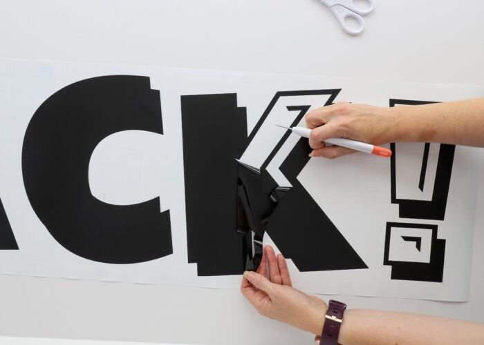 Horizontal image of black vinyl letters being weeded in preparation for layering