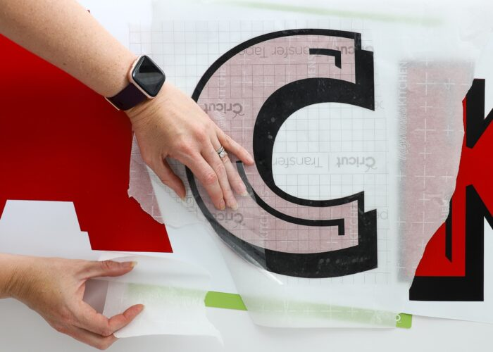 Hands using transfer tape and parchment paper to layer red and black vinyl letters