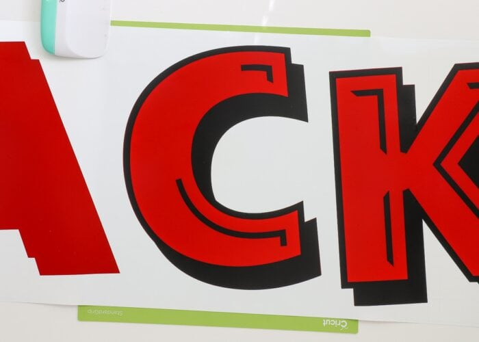 The letter C cut from red and black vinyl and layered together