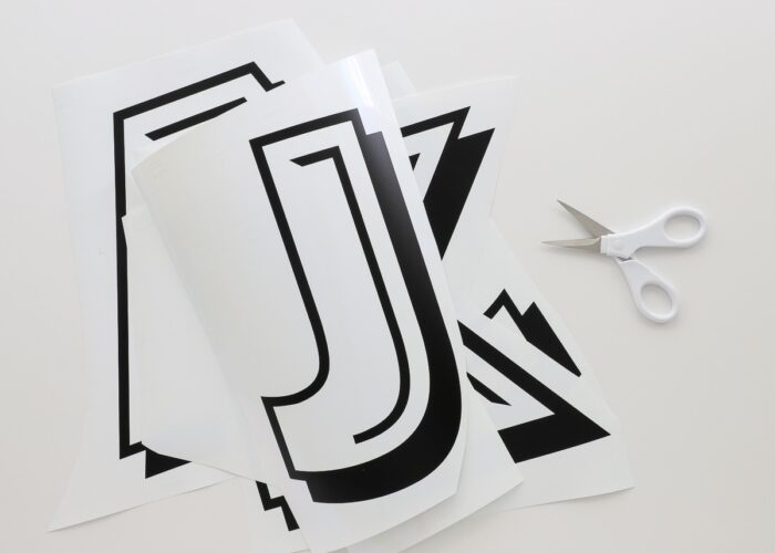 Horizontal image of black vinyl letters weeded in preparation for layering
