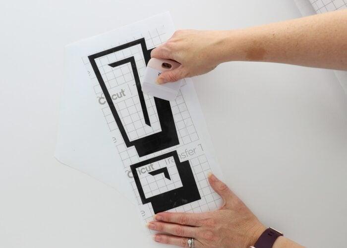 Hands using scraper on black vinyl letter