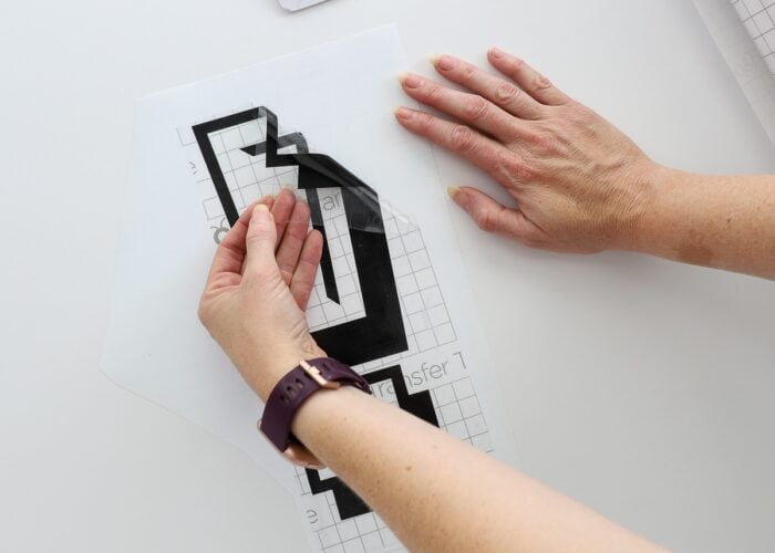Hands using transfer tape to pick up a black vinyl letter