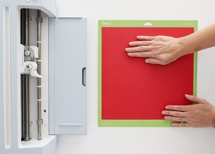 Cricut Maker 3 machine shown with a hand loading red paper onto a green Cricut mat