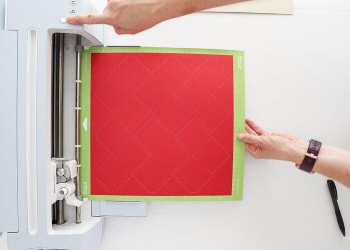 Hand loading a green Cricut mat with red paper into a Cricut Maker 3 machine.