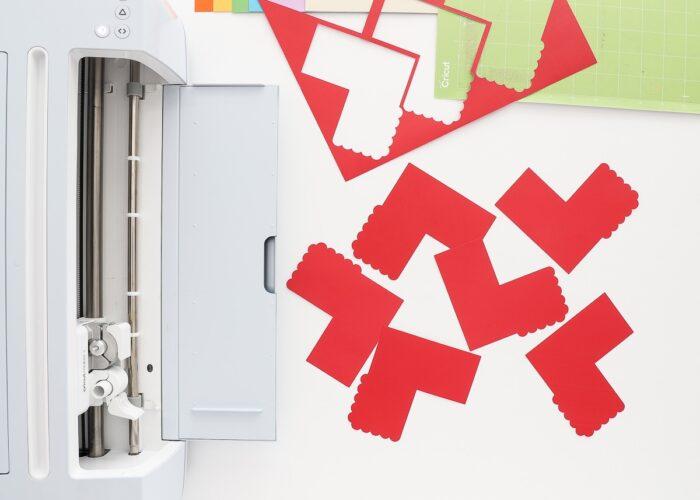 Cricut Maker 3 shown with red pencil bookmark cutouts.