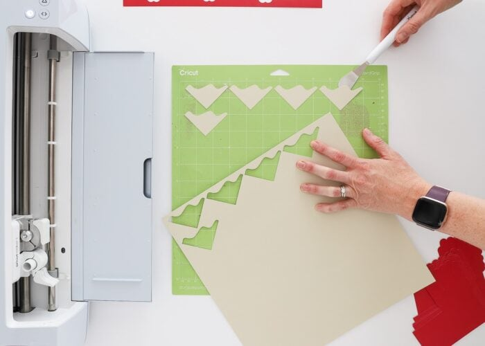 Hands removing tan cardstock from a Cricut mat.