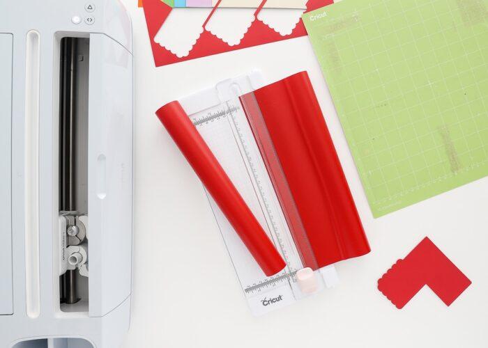 Cricut paper trimmer shown cutting down red vinyl.