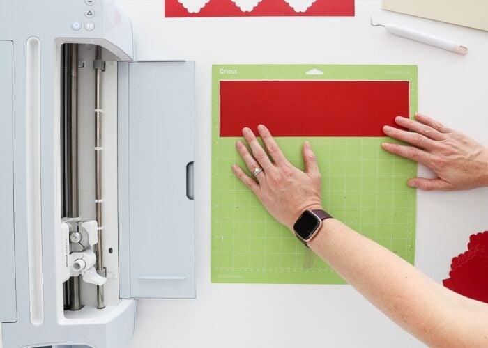 Hands loading red vinyl onto a green Cricut mat.
