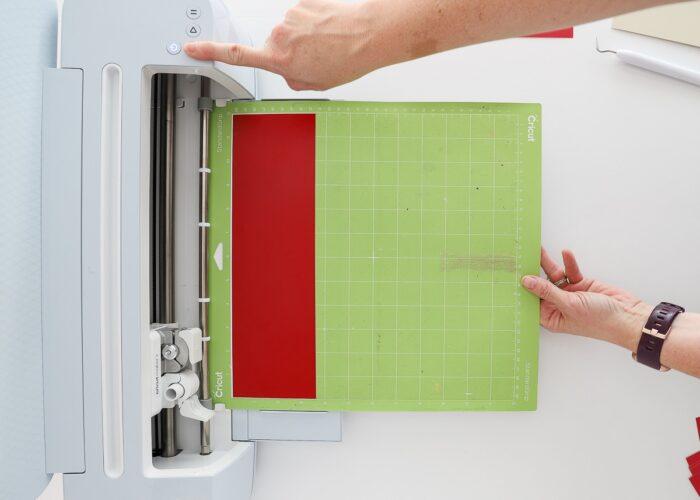 Hands loading a green Cricut mat into a Cricut Maker 3 machine.