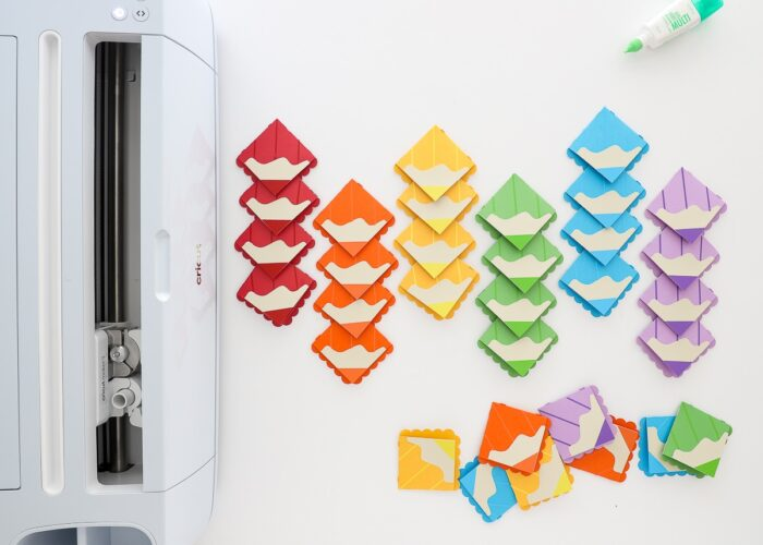 Cricut Maker 3 pictured with corner bookmarks made from paper to look like colored pencils.