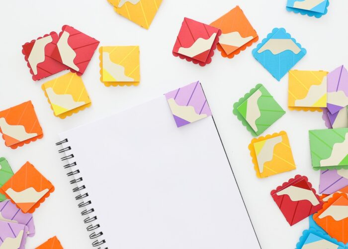 Corner bookmarks made from paper to look like colored pencils hooked onto the corners of notebooks..