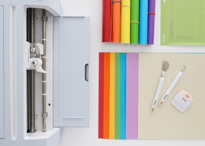 Cricut Maker 3 machine shown with rainbow colored cardstock and vinyl, as well as Cricut tools.