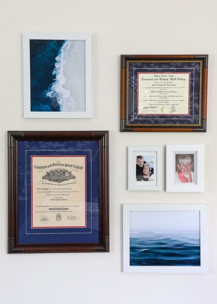 Small gallery wall with white and wood frames and ocean artwork.